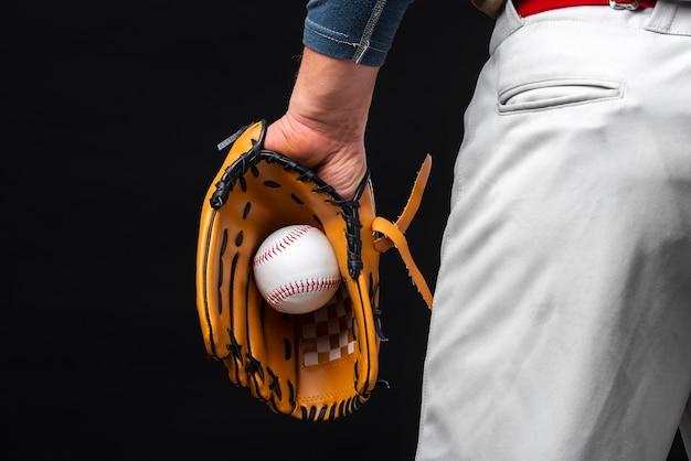 Punto di vista posteriore del guanto della tenuta dell'uomo con baseball