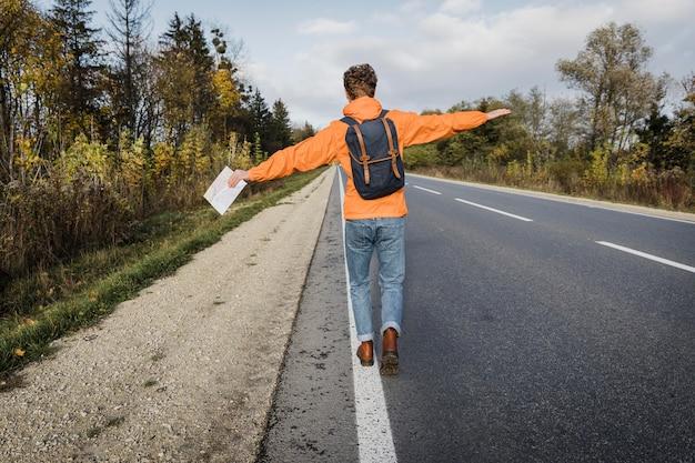Vista posteriore dell'uomo che tiene la mappa e cammina lungo la strada