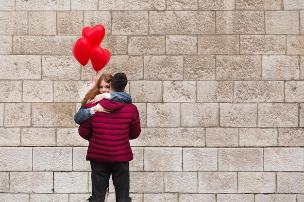 Vista posteriore uomo che abbraccia la fidanzata