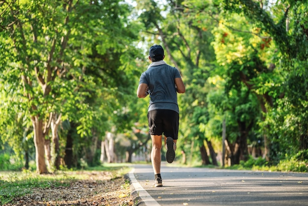 Back view of man jogging or running exercising outdoors in park, concept of healthy lifestyle.