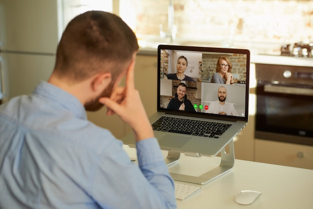 Back view of a man listening to his colleagues about business in a video meeting