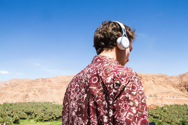 Back view of man listening to music in oasis