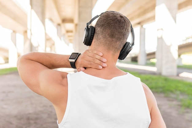 Back view man listening to music through headphones before training