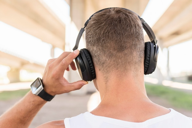 Back view man listening to music through headphones