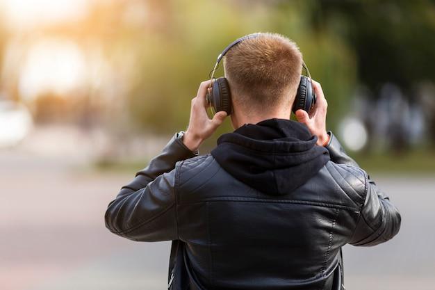 ヘッドフォンで音楽を聞いている背面図男