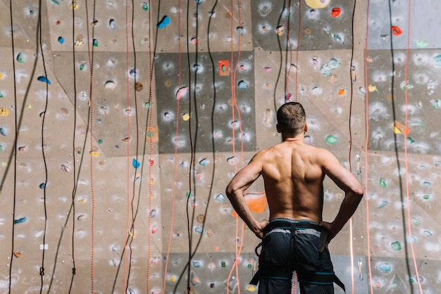 Back view man looking at climbing wall