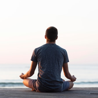 Вид сзади человек медитирует на пляже