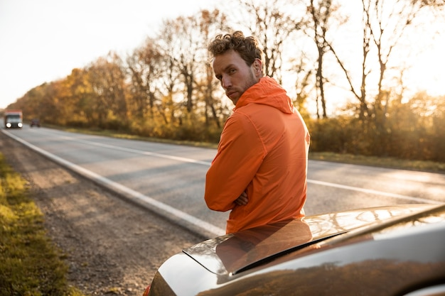 Back view of man posing next to car while on a road trip