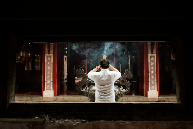 Back view of man praying at the temple with burning incense