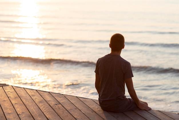 Вид сзади человек расслабляющий на пляже снаружи с копией пространства