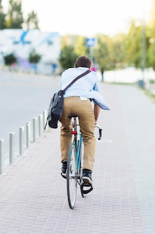 Back view man riding bike outdoors
