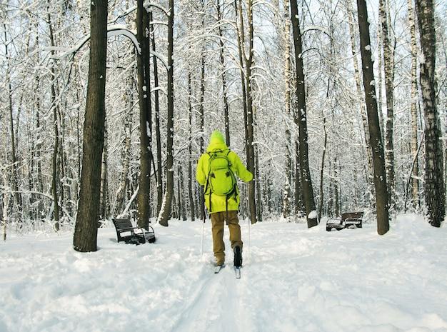 冬の森の背景でクロスカントリースキーで走っている男の背面図