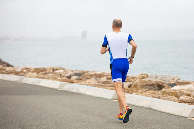 Back view of man running on sea coast
