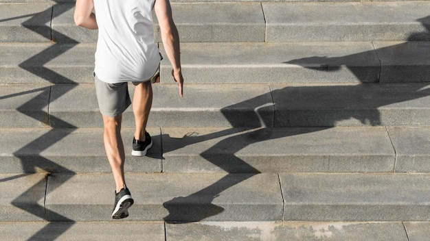 Back view man running on stairs with copy space