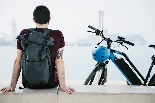 彼のeバイクの横に座っている背面図男