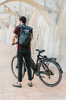 Back view of a man standing next to e-bike