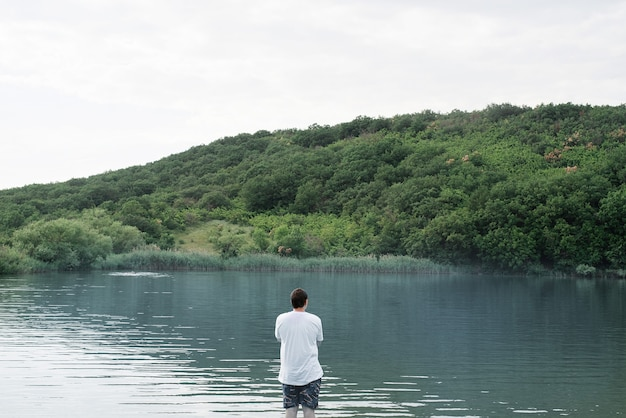 Back view of a man standing near the lake
