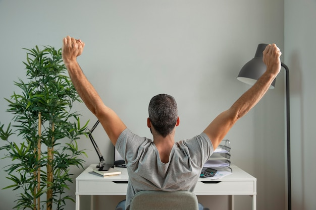 Back view of man stretching his arms while working from home