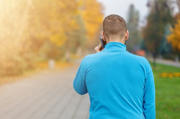 Back view of man talking on phone in autumn park