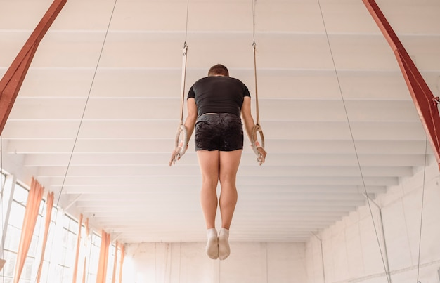 Тренировка человека на гимнастических кольцах, вид сзади