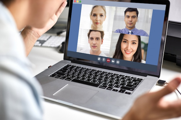 Back view of man using laptop video conference with corporate team