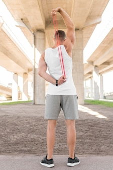 Back view man using a red stretching band
