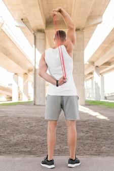 Vista posteriore uomo usando una fascia rossa che si estende
