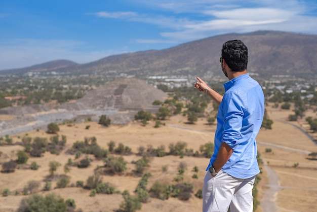 Back view of a man wearing a blue shirt on the background of san juan teotihuacan