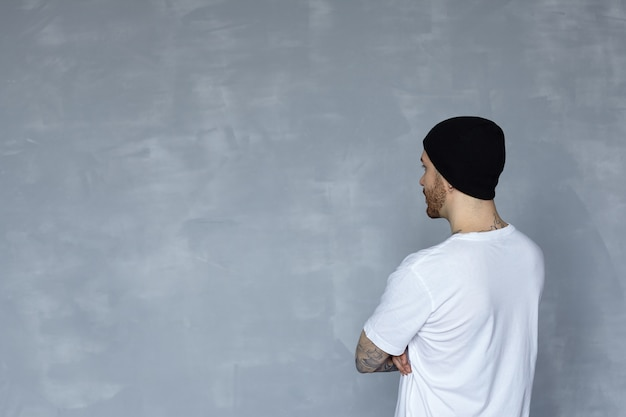 Back view on man in white t-shirt and black hat looks to grey wall