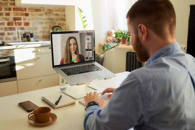 Back view of a man who works remotely talking to colleagues by a video call.