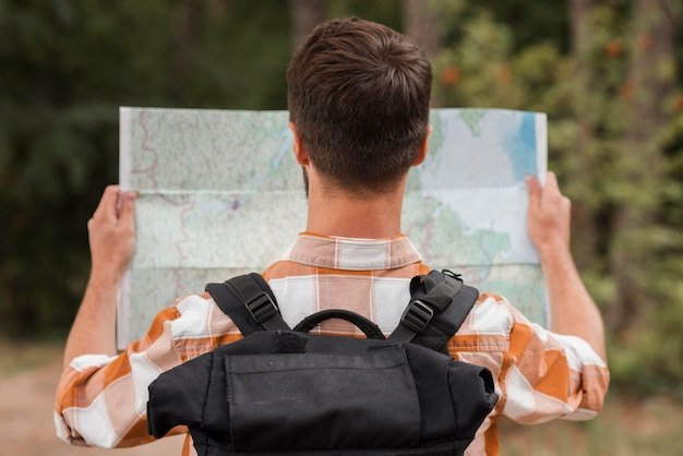 Back view of man with backpack looking at map while camping