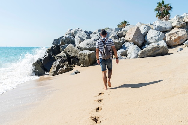Back view of a man with backpack walking away on seashore in a sunny day