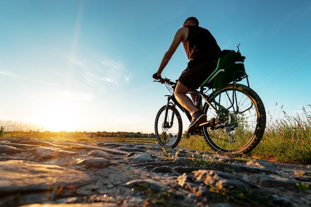 Back view of a man with a bicycle against the blue sky.