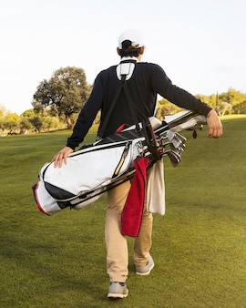 Back view of man with golf clubs on the field