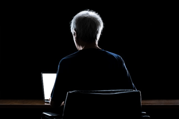 Back view of a man with gray hair working from home late at night using his laptop computer