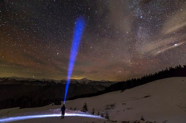 Back view of man with head flashlight standing on snowy valley under beautiful dark blue winter starry sky