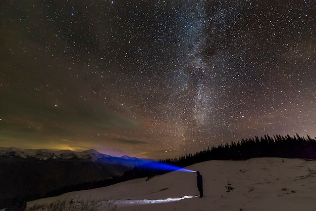 Back view of man with head flashlight standing on snowy valley