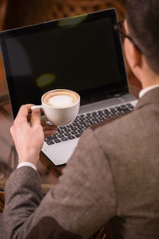 Back view of man with laptop and coffee at cafe.