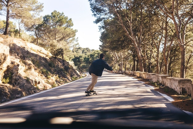 Back view of man with skateboard on road