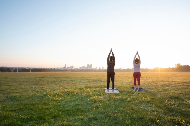 Back view of man and woman doing yoga together outdoors
