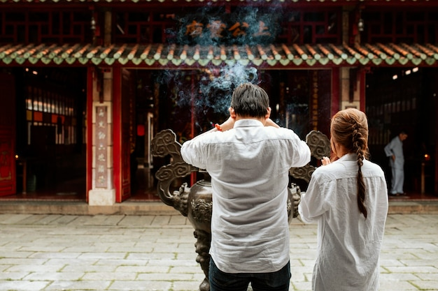 Back view of man and woman praying at the temple with burning incense