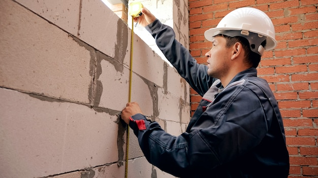 Back view of man working on site and measuring window in brick wall with ruler