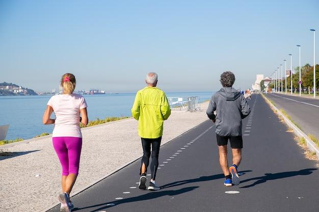 Vista posteriore di persone mature che indossano abiti sportivi, fare jogging lungo la riva del fiume. lunghezza intera. pensionamento o concetto di stile di vita attivo