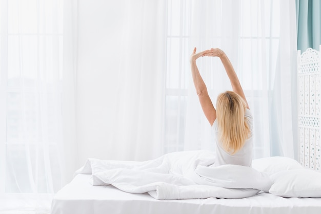 Back view mature woman waking up at home