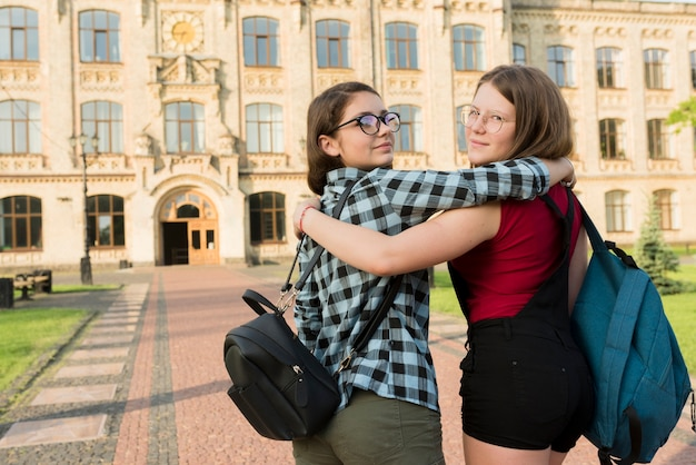 Вид сзади среднего снимка двух обнимающихся девочек-подростков, смотрящих на камеру
