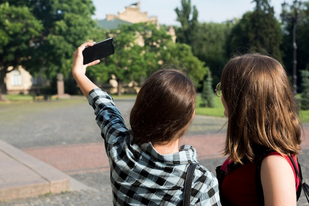 Back view medium shot of teenage girls taking a selfie