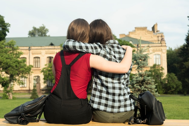 Back view medium shot of two teenage girls hugging