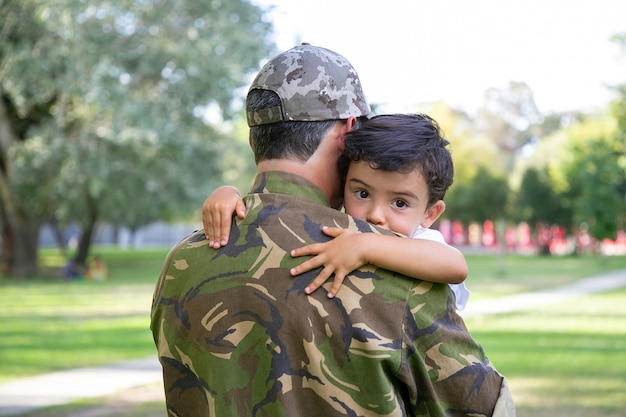 Back view of middle-aged father holding and embracing his son. lovely little boy hugging dad in army uniform and looking away.