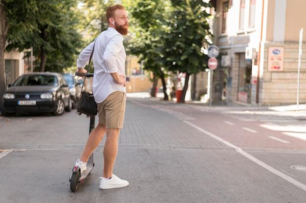 Вид сзади современного человека на скутере