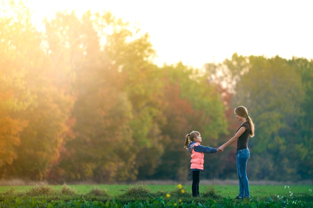 Back view of mother and child girl standing in green meadow holding hands